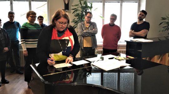 Vapaan säestyksen koulutuksen ohjaaja tekee merkintöjä paperiin flyygelin päällä.