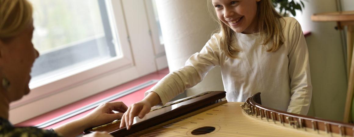 Nuori kanteleoppilas soittamassa yhdessä opettajan kanssa.