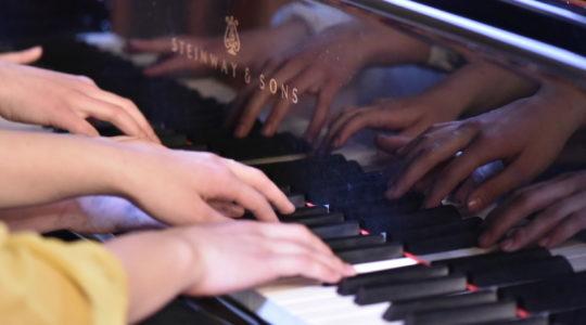 Flyygeliä soittavien nuorten kädet heijastuvat flyygelistä