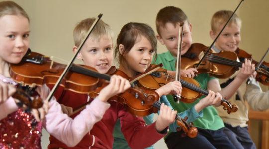 Opiston nuoria viulunsoittajia soittamassa yhdessä