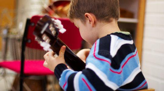 Nuori lapsi soittaa kitaraa