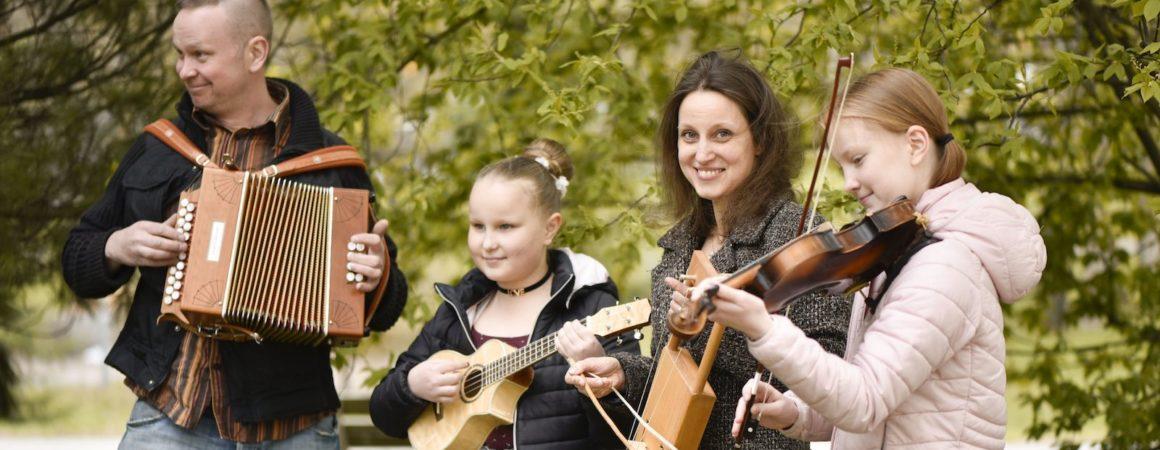 Kamulinjan nuoria ja aikuisia oppilaita soittamassa ulkona yhdessä