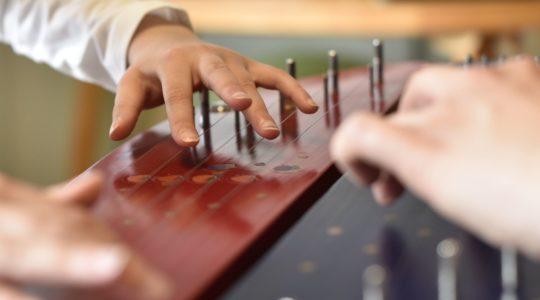 Kahden kanteleensoittajan kädet soittamassa viisikielistä kanteletta