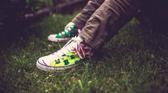 Nuori tennarit jalassa istumassa nurmikolla
