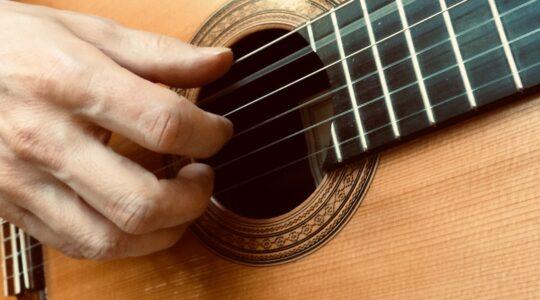akustinen kitara ja soittava käsi