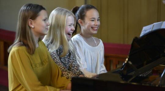 kolme pianistia soittamassa yhdessä flyygeliä