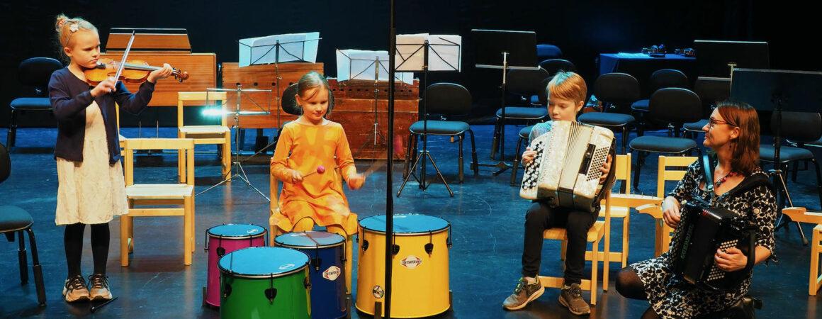 Kolme lasta ja aikuinen soittamassa viulua, rumpua ja haitaria esiintymislavalla